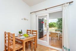 Обеденная зона. Испания, Менорка : Небольшие уютные современные апартаменты в нескольких метрах от песчаного пляжа, 2 спальни, ванная комната, общий басейн