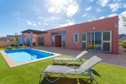 Вид на виллу/дом снаружи. Испания, Фуэртевентура : Очаровательная вилла для отдыха на испанском острове, с 3 спальнями, 3 ванными комнатами, а также отдельным бассейном с подогревом, бассейном и видом на море.