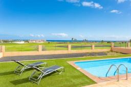 Зона отдыха у бассейна. Испания, Фуэртевентура : Яркая просторная вилла со всеми удобствами, с видом на море и поле для гольфа, с 3 спальнями, 3 ванными комнатами, а также отдельным бассейном с подогревом