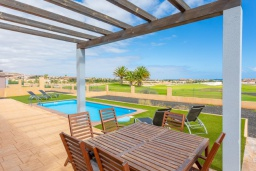 Терраса. Испания, Фуэртевентура : Яркая просторная вилла со всеми удобствами, с видом на море и поле для гольфа, с 3 спальнями, 3 ванными комнатами, а также отдельным бассейном с подогревом