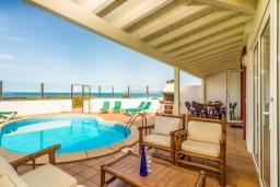 Вид на виллу/дом снаружи. Испания, Фуэртевентура : Двухэтажная вилла с частным бассейном, частично крытым внутренним двориком с садовой мебелью, кухонными принадлежностями на открытом воздухе и стеклянной балюстрадой с видом на пляж.